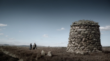 Claire & Frank, Culloden memorial cairn, head stones. Image by STARZ Sony Pictures Television, via Outlander-Online.com